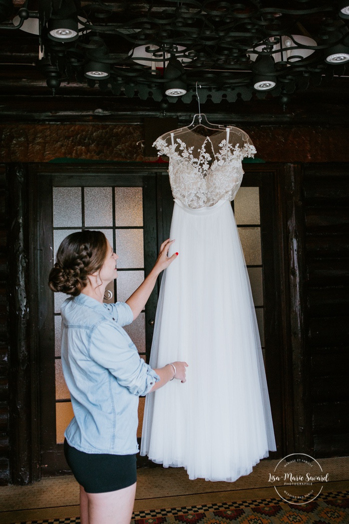 Bride looking at lace wedding dress hanging from ceiling. Mariage en Outaouais. Fairmont Le Château Montebello wedding. Ottawa photographer.