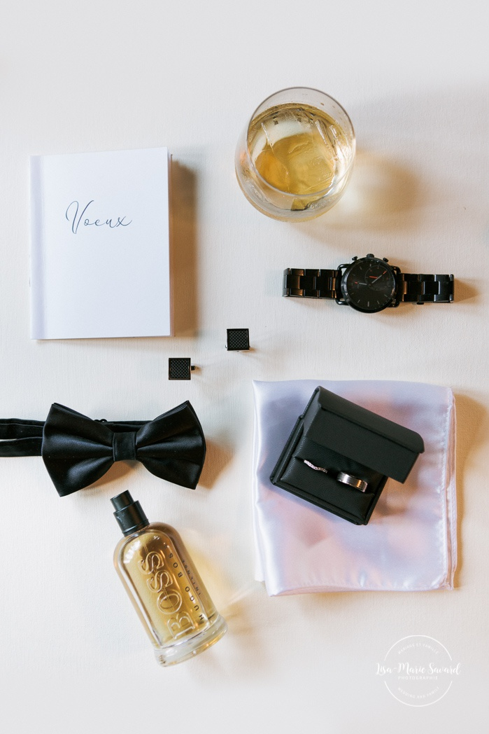 Wedding detail shots vow book, watch, cufflinks, bow tie, rings, handkerchief, Cologne and alcool. Mariage en Outaouais. Outaouais wedding. Ottawa photographer.