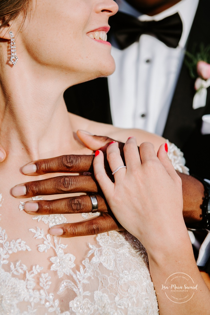 Close up on bride and groom hangs with wedding rings. African American groom and Caucasian bride. Mariage en Outaouais. Fairmont Le Château Montebello outdoor wedding. Ottawa photographer.