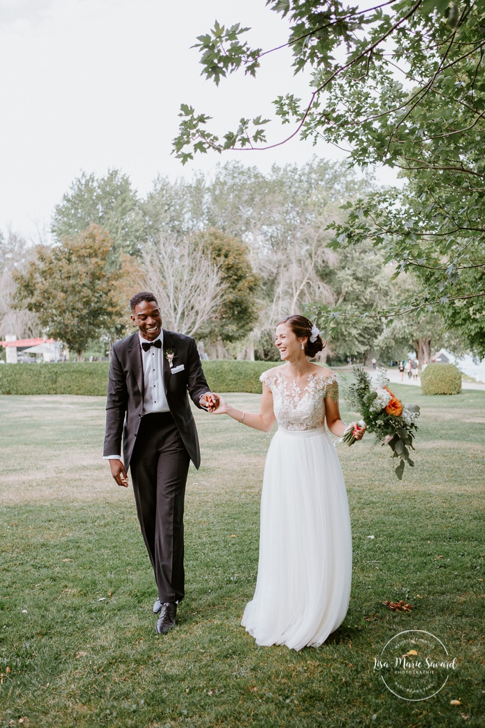 Bride and groom walking hand in hand. Mariage en Outaouais. Fairmont Le Château Montebello outdoor wedding. Ottawa photographer.