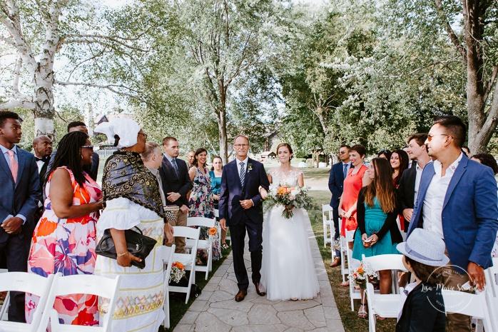 Outdoor wedding ceremony by the river. Bride walking down the aisle with father. Cérémonie de mariage extérieure au Château Montebello. Fairmont Le Château Montebello outdoor wedding. Ottawa photographer.