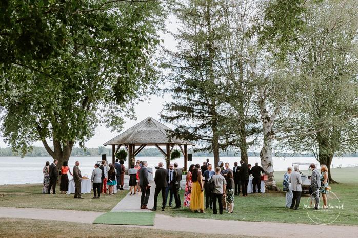 Outdoor wedding ceremony by the river. Cérémonie de mariage extérieure au Château Montebello. Fairmont Le Château Montebello outdoor wedding. Ottawa photographer.