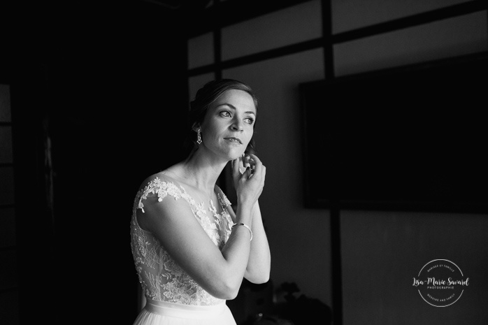 Bride putting on earrings before first look. Mariage en Outaouais. Fairmont Le Château Montebello wedding. Ottawa photographer.