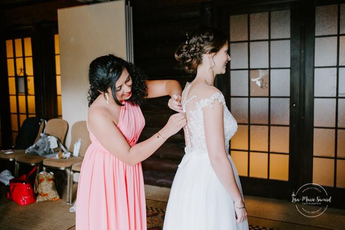 Bridesmaid buttoning the bride's dress. Mariage en Outaouais. Fairmont Le Château Montebello wedding. Ottawa photographer.