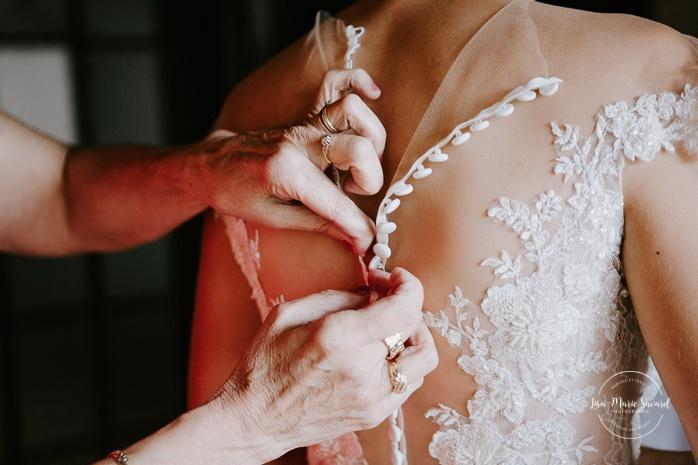 Mother buttoning the bride's dress. Mariage en Outaouais. Fairmont Le Château Montebello wedding. Ottawa photographer.