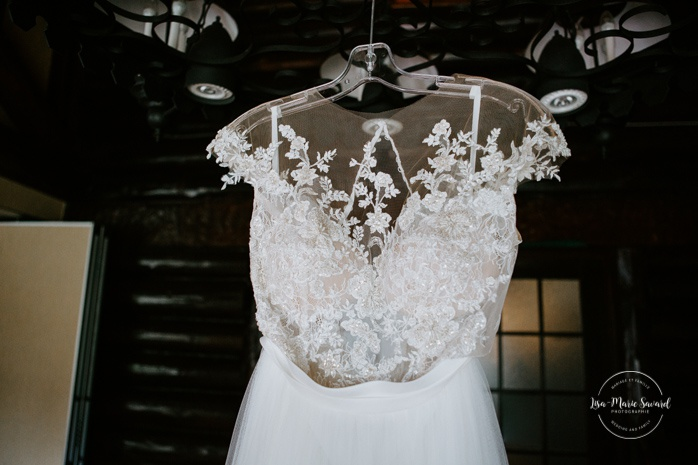 Lace wedding dress hanging from ceiling. Mariage en Outaouais. Fairmont Le Château Montebello wedding. Ottawa photographer.