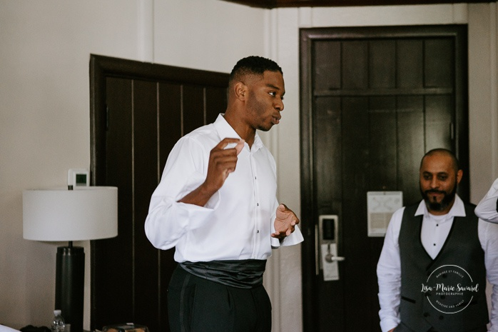 African American groom getting ready with groomsmen in hotel room. Mariage en Outaouais. Outaouais wedding. Ottawa photographer.