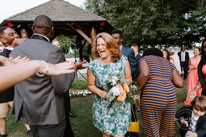 Outdoor bouquet toss during cocktail. African American groom and Caucasian bride. Mariage en Outaouais. Fairmont Le Château Montebello outdoor wedding. Ottawa photographer.