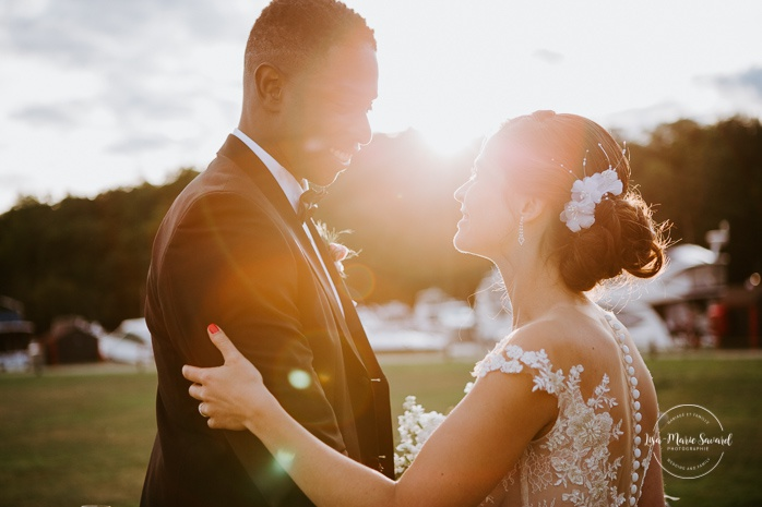 Bride and groom kissing in front of sunset flare. African American groom and Caucasian bride. Mariage en Outaouais. Fairmont Le Château Montebello outdoor wedding. Ottawa photographer.
