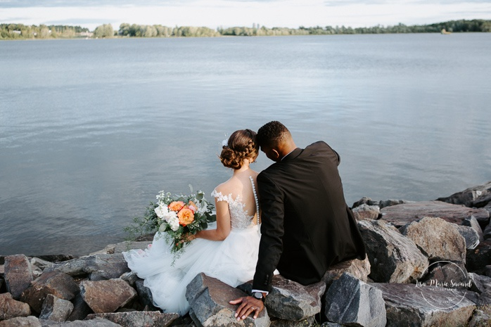 Bride and groom sitting on rocks by the river. African American groom and Caucasian bride. Mariage en Outaouais. Fairmont Le Château Montebello outdoor wedding. Ottawa photographer.