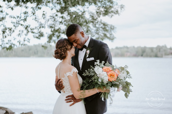 Groom kissing bride on the forehead by the river. African American groom and Caucasian bride. Mariage en Outaouais. Fairmont Le Château Montebello outdoor wedding. Ottawa photographer.