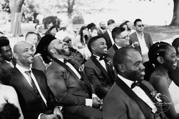 Outdoor wedding ceremony by the river. Groomsmen laughing during ceremony. Cérémonie de mariage extérieure au Château Montebello. Fairmont Le Château Montebello outdoor wedding. Ottawa photographer.