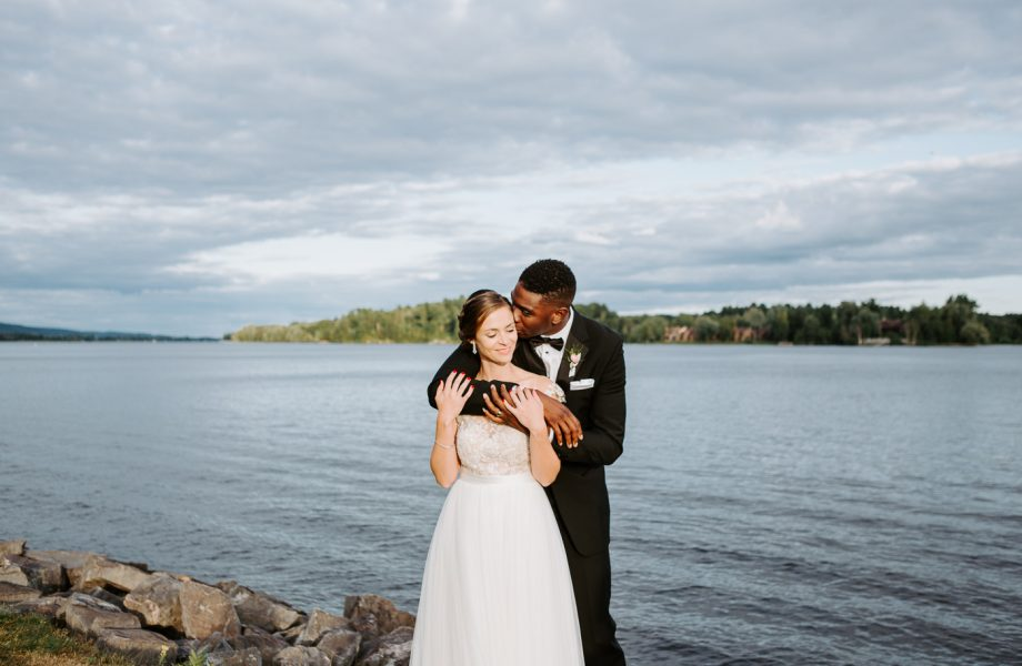 Bride and groom kissing by the river. African American groom and Caucasian bride. Mariage en Outaouais. Fairmont Le Château Montebello outdoor wedding. Ottawa photographer.