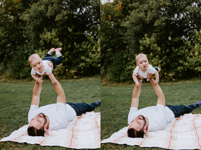 Dad lifting baby in the air on a blanket outside. Outdoor family photos with three months old baby boy. Three months milestones. Family photos at the park. Photographe de famille à Montréal.