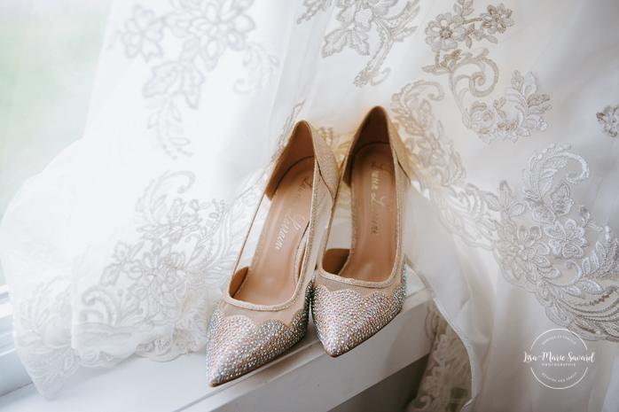 Bride's shoes in front of lace wedding dress. Asian bride getting ready with four bridesmaids. Mariage à l'Orée des Champs en automne. Orée des Champs Saint-Nazaire Saguenay-Lac-Saint-Jean. Photographe de mariage Saguenay.