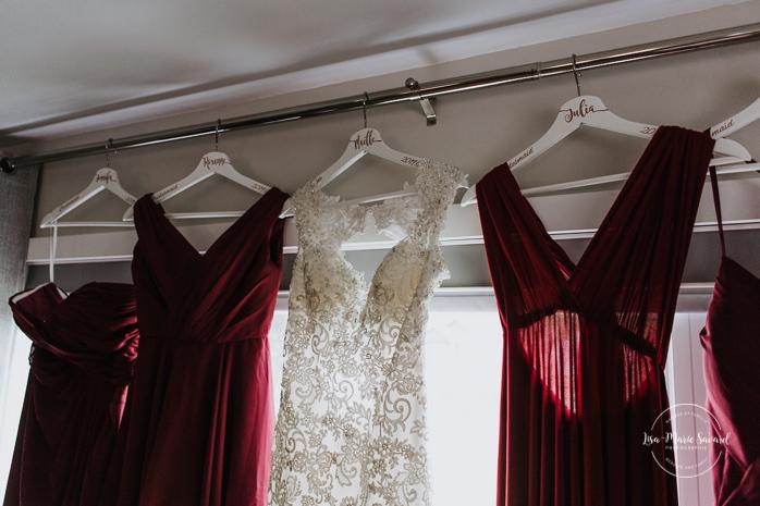 Wedding dresses hanging in front of window. Asian bride getting ready with four bridesmaids. Mariage à l'Orée des Champs en automne. Orée des Champs Saint-Nazaire Saguenay-Lac-Saint-Jean. Photographe de mariage Saguenay.