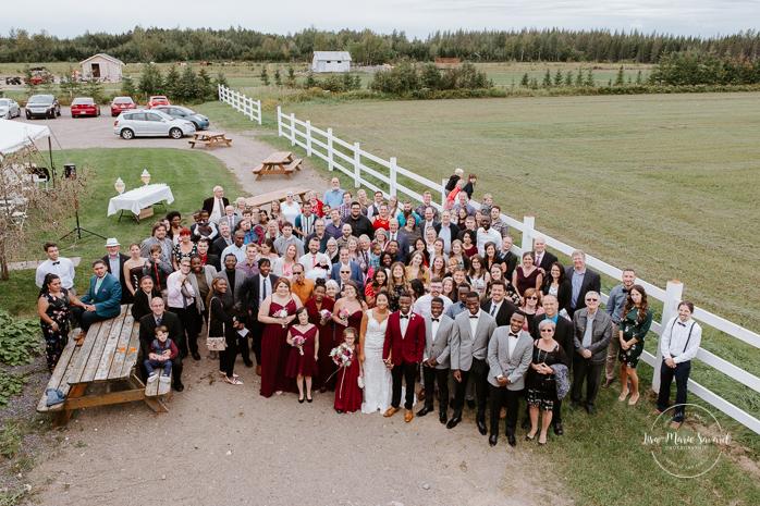 Large wedding group photo shot from balcony. Mariage à l'Orée des Champs en automne. Orée des Champs Saint-Nazaire Saguenay-Lac-Saint-Jean. Photographe de mariage Saguenay.
