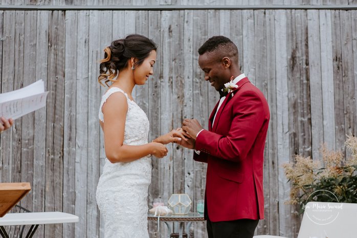 Fall barn wedding. Fall outdoor wedding ceremony. Bride and groom exchanging rings. Mixed wedding with Asian bride and Black groom. Mariage à l'Orée des Champs en automne. Orée des Champs Saint-Nazaire Saguenay-Lac-Saint-Jean. Photographe de mariage Saguenay