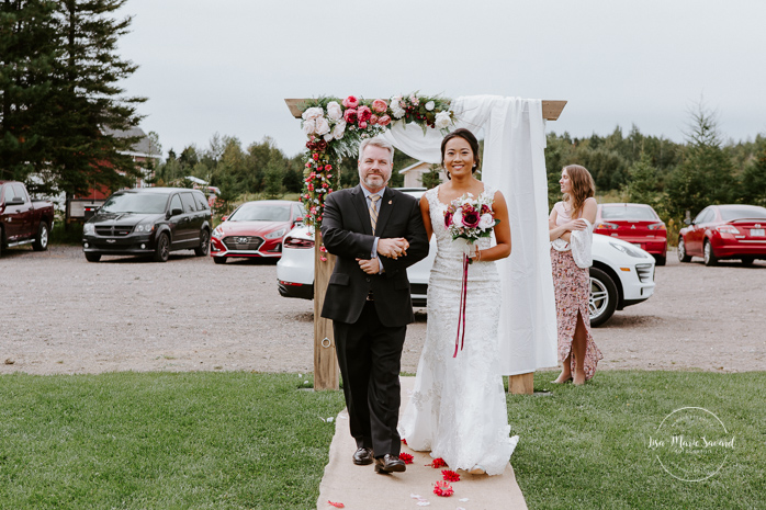 Bride walking down with aisle with big brother. Fall barn wedding. Fall outdoor wedding ceremony. Mixed wedding with Asian bride and Black groom. Mariage à l'Orée des Champs en automne. Orée des Champs Saint-Nazaire Saguenay-Lac-Saint-Jean. Photographe de mariage Saguenay.