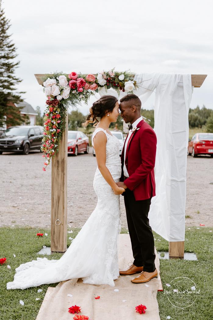 Bride and groom in front of floral arch. Asian bride and Black groom wedding photos. Mariage en automne au Saguenay. Saint-Nazaire Saguenay-Lac-Saint-Jean. Photographe de mariage Saguenay.