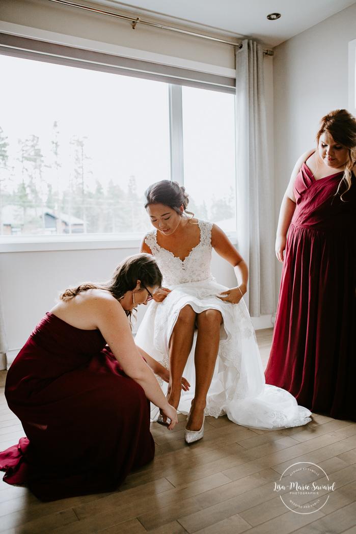 Bridesmaids helping bride put on shoes. Asian bride getting ready with four bridesmaids. Mariage à l'Orée des Champs en automne. Orée des Champs Saint-Nazaire Saguenay-Lac-Saint-Jean. Photographe de mariage Saguenay.
