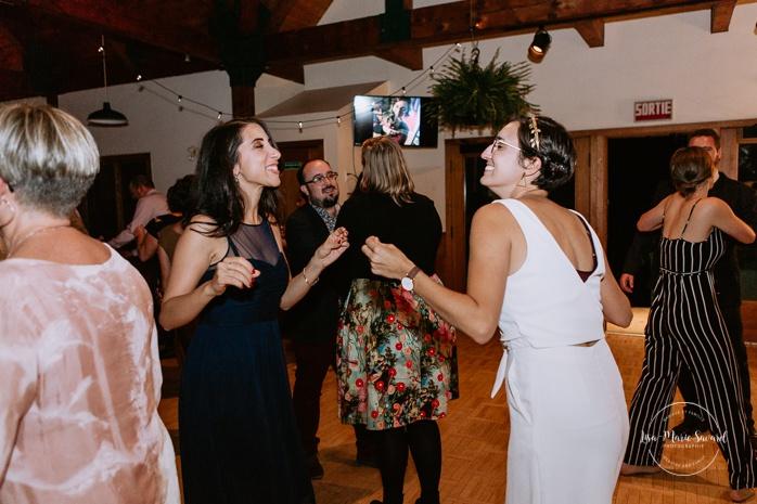 Wedding guests dancing on the dance floor. Same sex wedding photos. Lesbian wedding photos. Intimate summer camp LGBTQ+ wedding. Mariage au Cap-Saint-Jacques à Pierrefonds. Mariage LGBTQ+ à Montréal. Montreal LGBTQ+ wedding.
