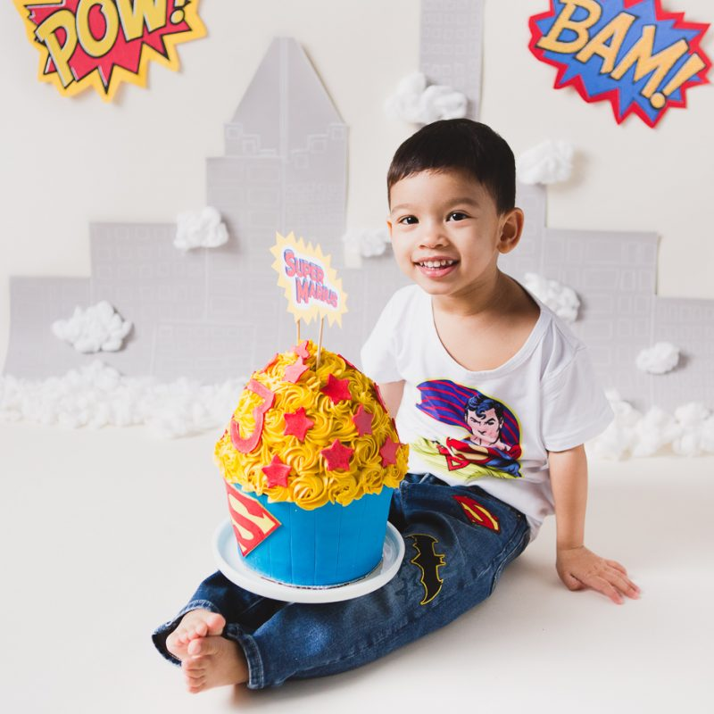 Superhero Smash the Cake session. Personalized Superman Cake Smash session. Superhero birthday ideas. Smash the Cake de super-héros à Montréal. Photographe de Cake Smash à Montréal
