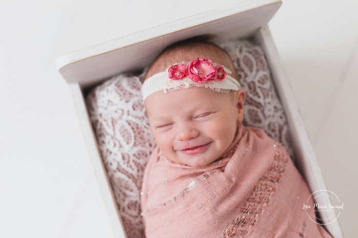 Newborn girl smiling. Minimalist girl newborn session. White wooden bed. Newborn photos pink. Organic floral headband newborn. Photos de nouveau-né à Verdun. Verdun newborn photographer.