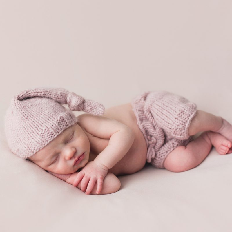 Lilac purple newborn photos. Newborn girl laying sideways with night cap. Minimalist girl newborn session. Organic newborn photos. Pure newborn photos. Photos de nouveau-né à Verdun. Verdun newborn photographer.