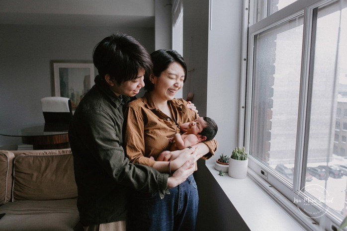 Intimate in-home newborn session. Lifestyle newborn photos. Parents holding baby next to window. Photoshoot de bébé à Montréal. Old Montreal newborn photographer. Montreal travel photographer.