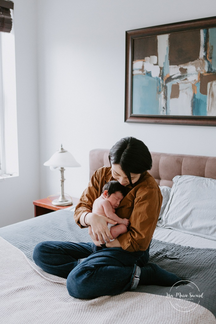 Intimate in-home newborn session. Lifestyle newborn photos. Mom holding baby on bed. Photoshoot de bébé à Montréal. Old Montreal newborn photographer. Montreal travel photographer.