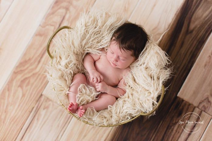 Newborn baby in basket with fur. Minimalist newborn session. Baby photos ideas. Photos de nouveau-né avec parents à Montréal. Montreal newborn photos with parents. Photographe à Verdun. Verdun photographer