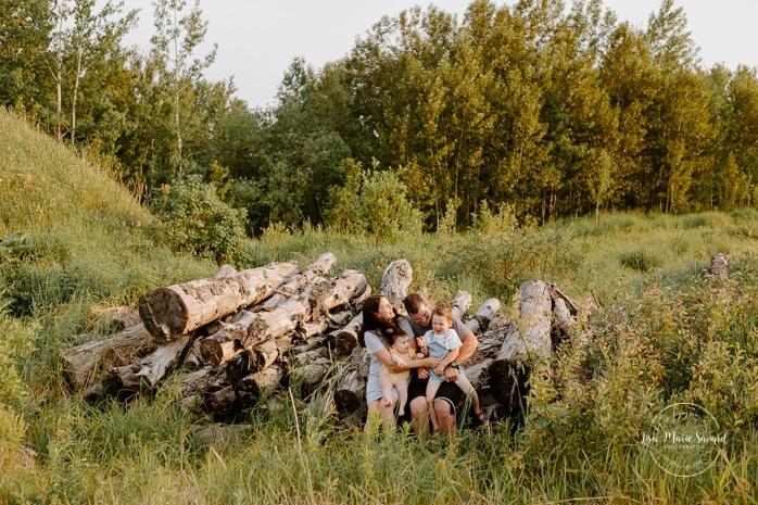 Family photos in a field. Golden hour family photos. Family sitting on stack wood. Séance photo dans un champ sauvage. Photographe de famille au Saguenay-Lac-Saint-Jean. Saguenay family photographer.