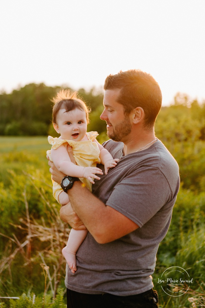 Family photos in a field. Golden hour family photos. Dad and daughter. Dad holding baby girl. Séance photo dans un champ sauvage. Photographe de famille au Saguenay-Lac-Saint-Jean. Saguenay family photographer.