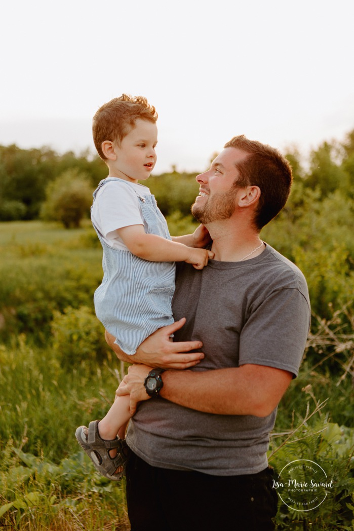 Family photos in a field. Golden hour family photos. Dad and son. Dad playing with toddler son. Séance photo dans un champ sauvage. Photographe de famille au Saguenay-Lac-Saint-Jean. Saguenay family photographer.