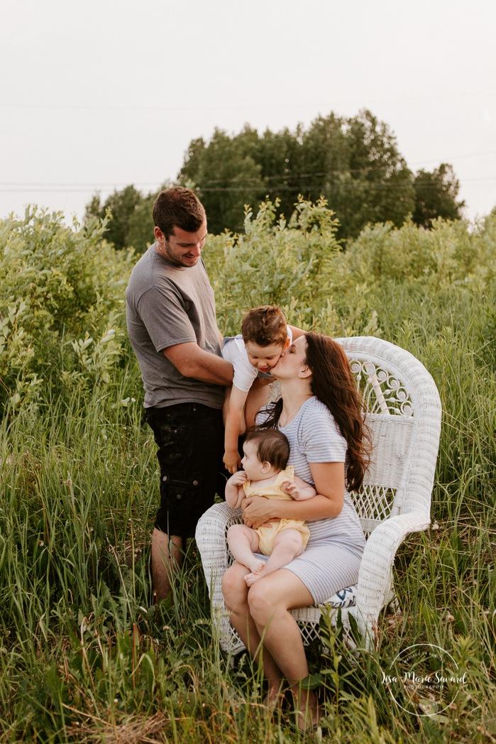 Family photos in a field. Family photos with wicker chair. Golden hour family photos. Family of four photos. Séance photo dans un champ sauvage. Photographe de famille au Saguenay-Lac-Saint-Jean. Saguenay family photographer.