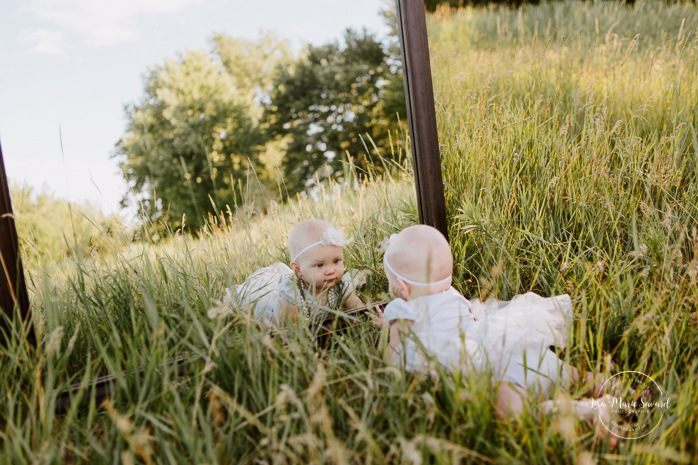 Six months old girl looking in mirror. Baby looking in mirror. Baby photos with mirror ideas. Outdoor family mini session. Family photos in a field. Photographe de famille à Montréal. Montreal riverbanks family photos. Montreal family photographer