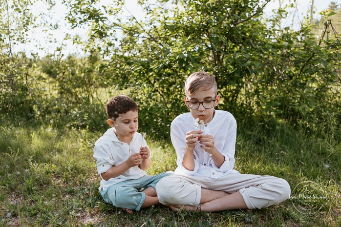 Boys blowing dandelions. Boys playing together. Big brother and little brother. Brothers playing together. Sibling photos. Outdoor family photos. Fun family photos. Photos de famille au Lac-Saint-Charles.