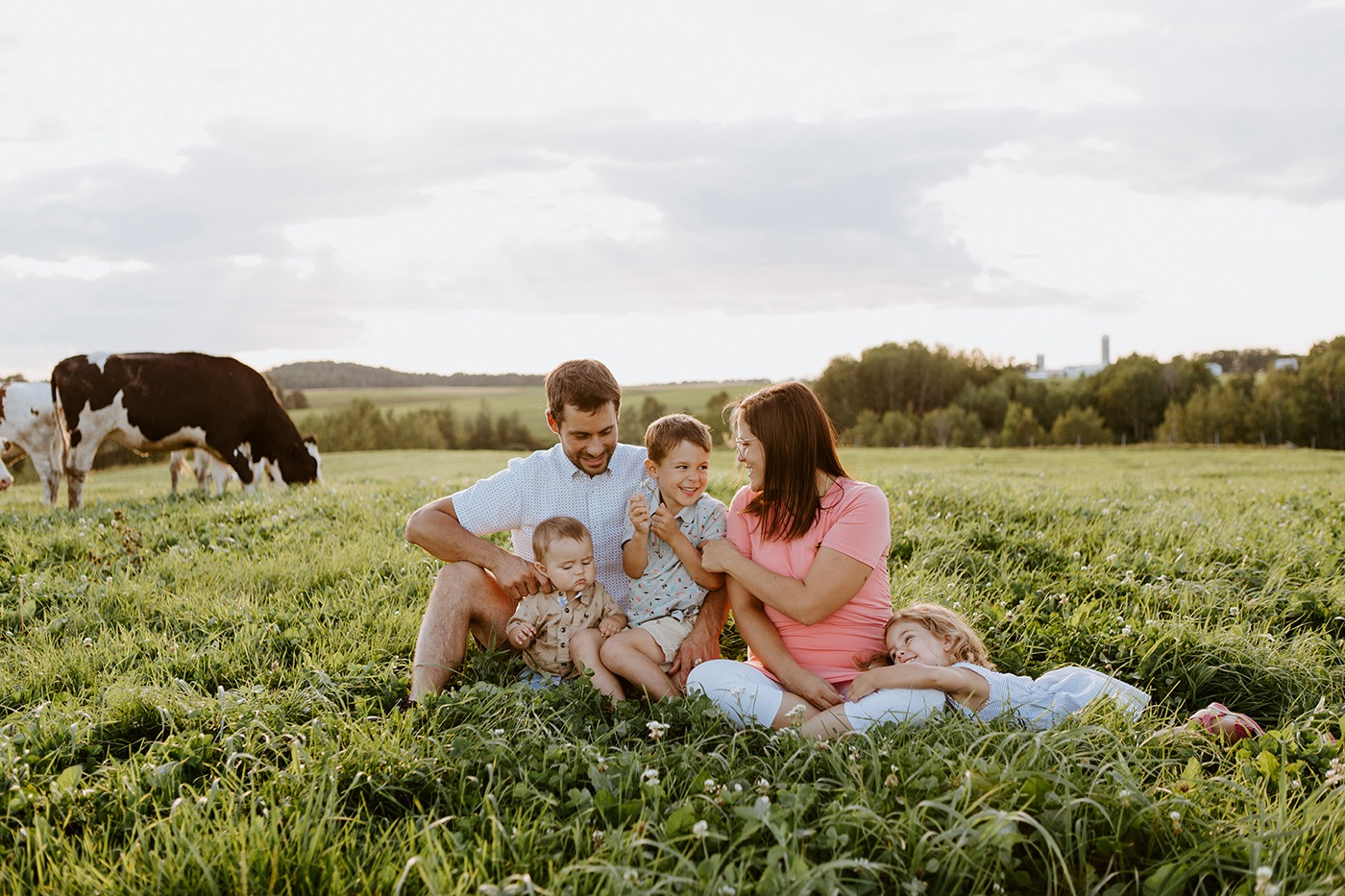 Dairy farm photos with cows. Farm photo session. Family photos with cows. Countryside family photos. Séance photo à la ferme avec des vaches. Séance photo ferme laitière. Photographe de famille à Montréal. Montreal family photographer.