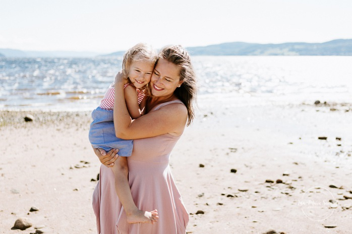 Beach family photos. Beach family session. Mom hugging toddler girl. Photos à la plage de La Baie quai d'escale. Photographe de famille au Saguenay. Saguenay family photographer.