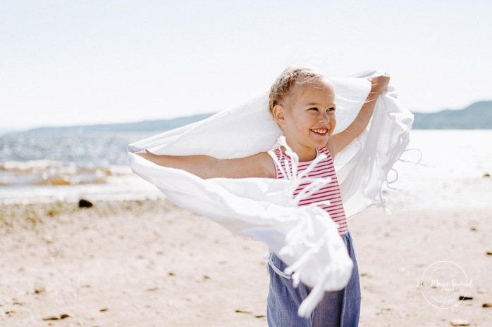 Beach family photos. Beach family session. Little girl holding scarf in the wind. Photos à la plage de La Baie quai d'escale. Photographe de famille au Saguenay. Saguenay family photographer.