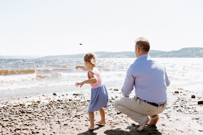 Beach family photos. Beach family session. Dad and toddler girl throwing rocks in the water. Photos à la plage de La Baie quai d'escale. Photographe de famille au Saguenay. Saguenay family photographer.