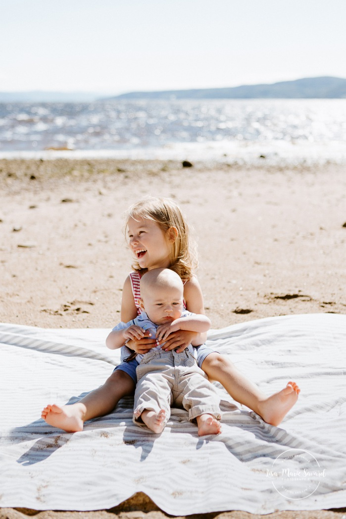 Beach family photos. Beach family session. Big sister holding little brother. Photos à la plage de La Baie quai d'escale. Photographe de famille au Saguenay. Saguenay family photographer.