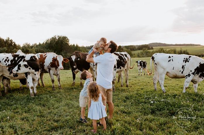 Dad throwing baby in air. Dairy farm photos with cows. Farm photo session. Family photos with cows. Countryside family photos. Photos de famille à la campagne. Photos de famille dans un champ. Photographe de famille à Montréal. Montreal family photographer.