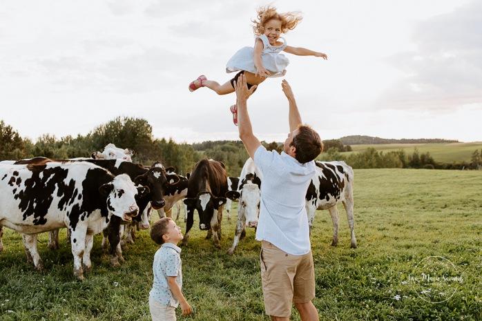 Dad throwing toddler girl in air. Dairy farm photos with cows. Farm photo session. Family photos with cows. Countryside family photos. Photos de famille à la campagne. Photos de famille dans un champ. Photographe de famille à Montréal. Montreal family photographer.