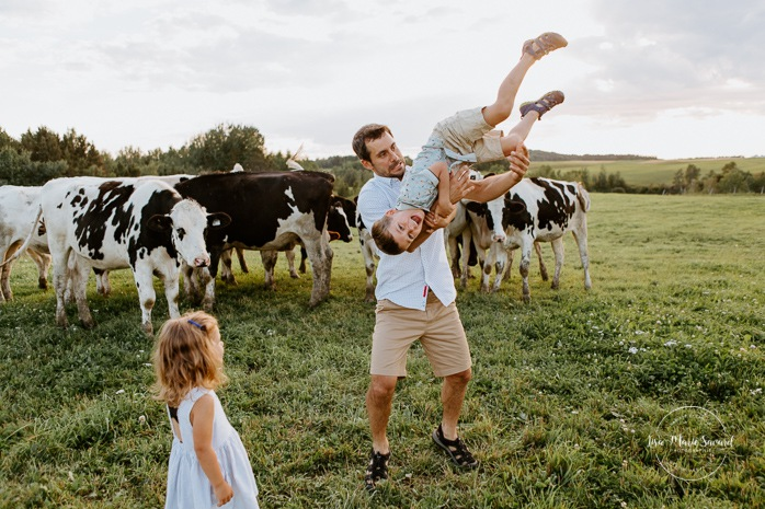 Dad playing fight with little boy. Dairy farm photos with cows. Farm photo session. Family photos with cows. Countryside family photos. Photos de famille à la campagne. Photos de famille dans un champ. Photographe de famille à Montréal. Montreal family photographer.