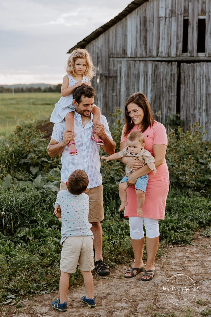 Family photos in front of old barn. Barn family photos. Dairy farm photos with cows. Farm photo session. Family photos with cows. Countryside family photos. Photos de famille à la campagne. Photos de famille dans un champ. Photographe de famille à Montréal. Montreal family photographer.