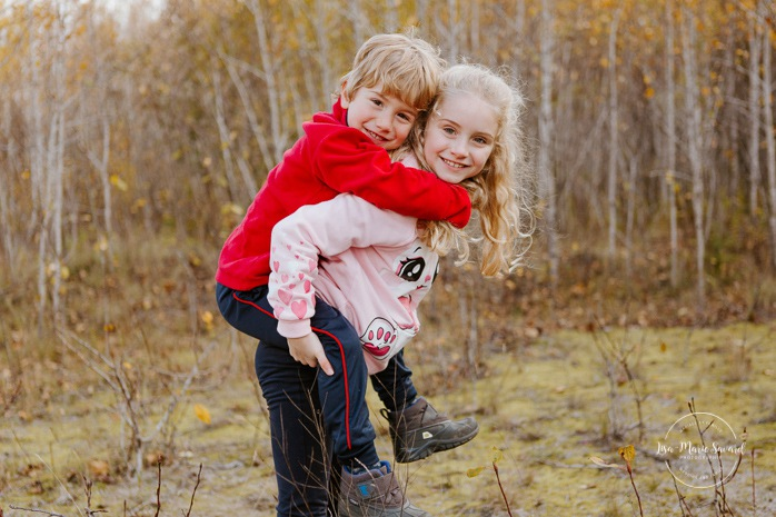 Fall family photos. Autumn family session. Older sister holding younger brother on her back. Sibling photos. Sister and brother photos. Minis séances d'automne au Saguenay. Photos de famille à Jonquière. Saguenay family photographer.