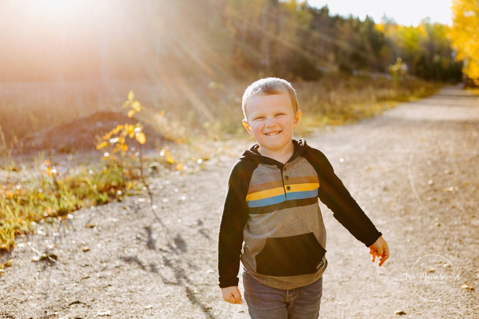 Fall family photos. Autumn family session. Boy smiling at the camera with sun flare. Mischievous boy smiling. Minis séances d'automne au Saguenay. Photos de famille à Jonquière. Saguenay family photographer.