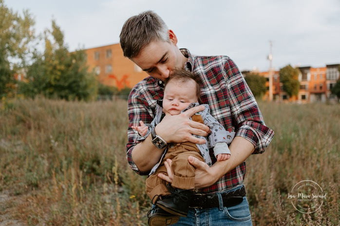 Outdoor lifestyle newborn session. Dad holding baby boy closely. Parc Pierre-Dansereau. Photo de bébé à domicile à Montréal. Montreal in-home baby session. Photographe de bébé à Montréal. Montreal baby photographer.